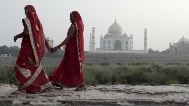 vídeos de stock, filmes e b-roll de women wearing saris, walking past taj mahal. india. - patrimônio mundial da unesco