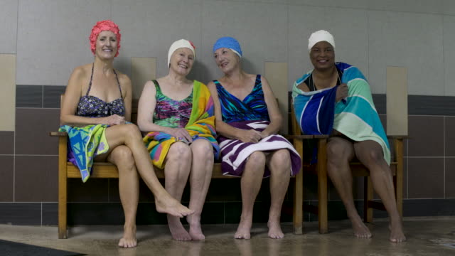 Women wearing swimming caps on poolside chatting, looking at camera smiling.