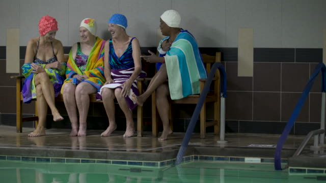 women wearing swimming caps on poolside chatting. - swimming cap stock videos and b-roll footage
