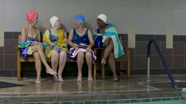 women wearing swimming caps on poolside chatting. - handtuch stock-videos und b-roll-filmmaterial