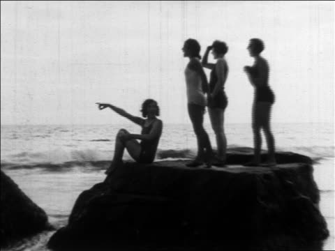 vídeos y material grabado en eventos de stock de b/w 1930 women wearing swimsuits sitting on rock at beach pointing offscreen / los angeles - traje de baño de una pieza