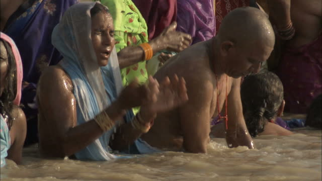 MS PAN  Women wearing thin veils and men bath in the Ganga river / Varanasi, Uttar Pradesh, India