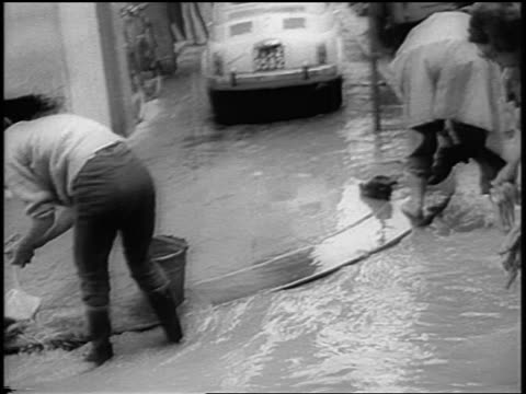 pan women wetting cloths shoes in flooded street / florence italy - anno 1966 video stock e b–roll