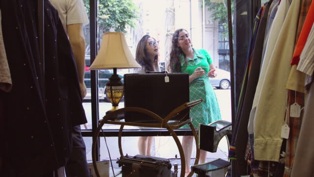 vídeos de stock e filmes b-roll de women window shopping outside vintage clothing store - fora de moda estilo