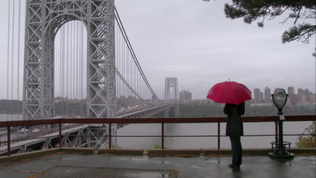 vídeos de stock, filmes e b-roll de women with a red umbrella looks at the george washington bridge. - chapéu