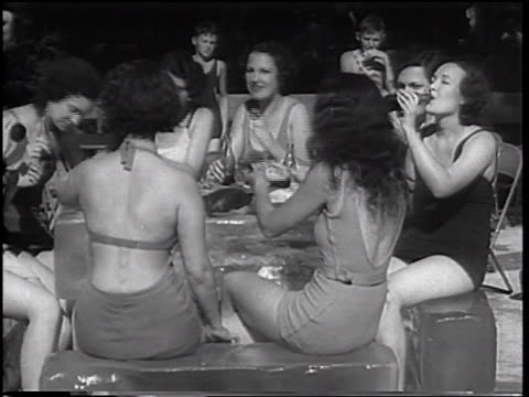 B/W 1933 women with bathing suits sitting + sipping cola on large blocks of ice / Coney Island, NY