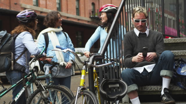 ms women with bicycles while man sitting on steps using mobile phone / portland, oregon, usa - see other clips from this shoot 1695 stock videos & royalty-free footage