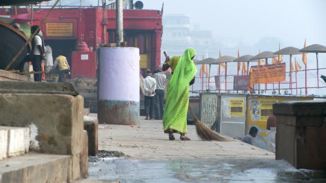 women with broom cleaning street - ドラム容器点の映像素材/bロール