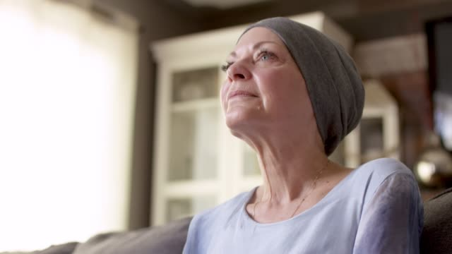 a women with cancer sits on her couch at home - survival stock videos & royalty-free footage