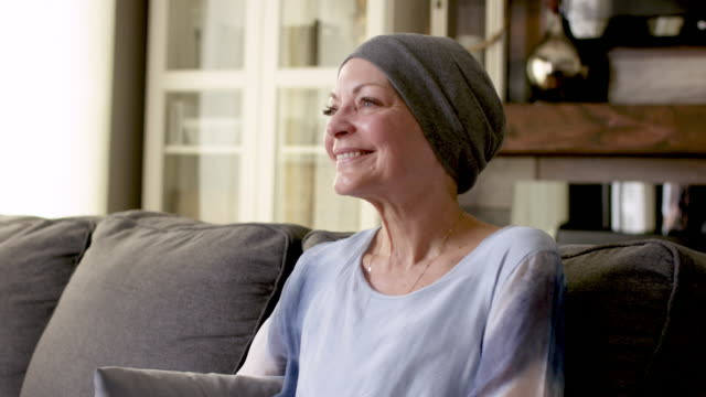 a women with cancer sits on her couch at home - courage stock videos & royalty-free footage