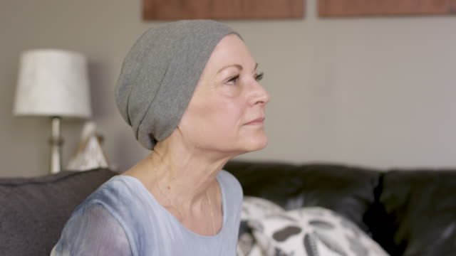 a women with cancer sits on her couch at home - fatcamera stock videos and b-roll footage