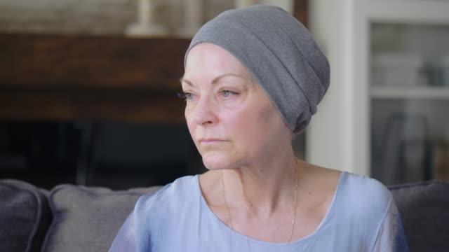 vídeos de stock, filmes e b-roll de as mulheres com cancro sentam-se em seu sofá em casa - radioterapia