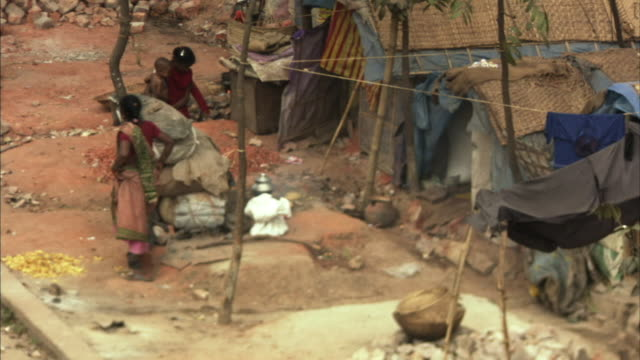 ha, ms, pan, women with child standing by tent in shanty town across wall from rickshaw riders standing on city street side, dhaka, bangladesh - dhaka stock-videos und b-roll-filmmaterial
