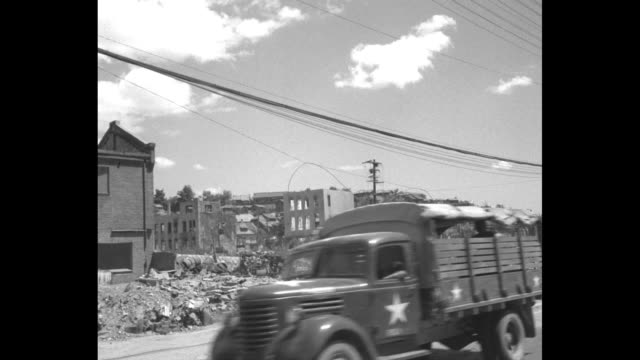 women with children hurry across street / vs army jeeps and trucks on road pass destroyed buildings / korean man sits on curb amidst debris holding... - korean war stock videos & royalty-free footage