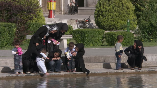 ms women with children playing by fountain at naghsh-e jahan square, isfahan, iran - iran video stock e b–roll