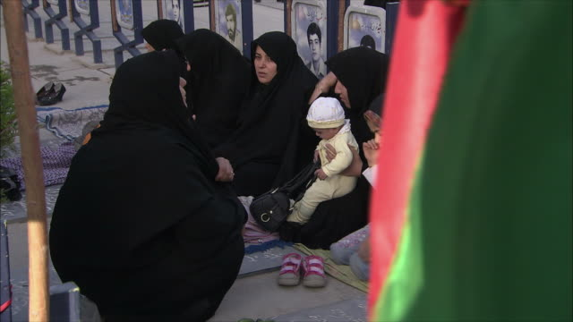 ms women with children sitting at iraq war cemetery, esfahan, iran - burka stock videos and b-roll footage