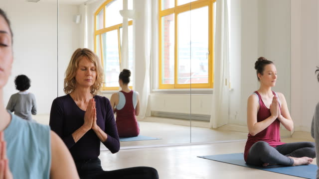 Women with closed eyes meditating in yoga class