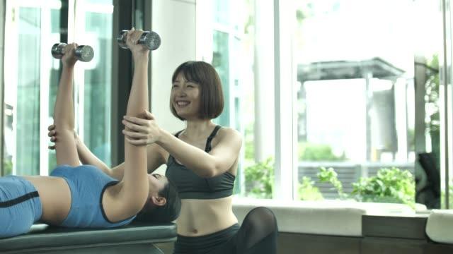 胸筋トレーニング スポーツとしてのバーベルを持ち上げるジムでフィットネス トレーナーと女性運動します。 - インストラクター点の映像素材/bロール