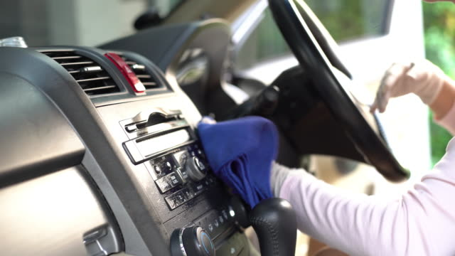a women with hand glove wiping down on surfaces of car interior for cleaning covid-19 virus - dustman stock videos & royalty-free footage