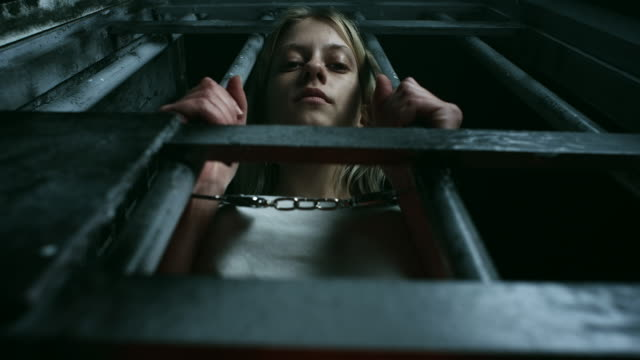 women with handcuffs holding bars and looking through - claustrophobia stock videos & royalty-free footage