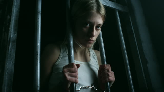 women with handcuffs holding bars and looking through - prisoner stock videos & royalty-free footage