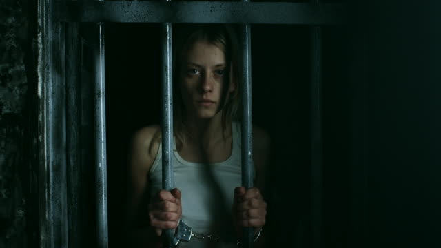 Women with handcuffs holding bars and looking through