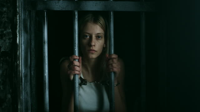 women with handcuffs holding bars and looking through - trapped stock videos & royalty-free footage