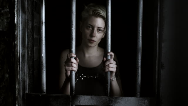 women with handcuffs holding bars and looking through - claustrophobia stock videos and b-roll footage