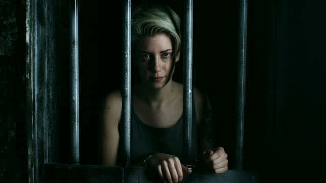 women with handcuffs holding hands betwen bars and looking through - claustrophobia stock videos & royalty-free footage