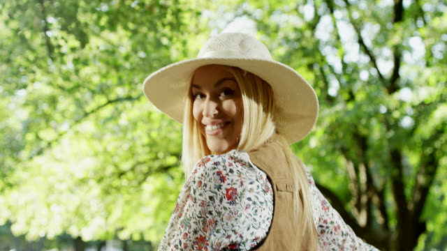 vídeos de stock e filmes b-roll de women with hat turning head at park - cabeça humana