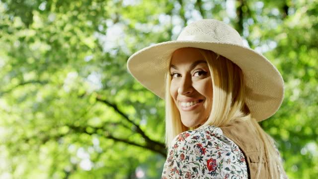 vídeos de stock, filmes e b-roll de mulheres com chapéu, virando a cabeça no parque - cabelo louro