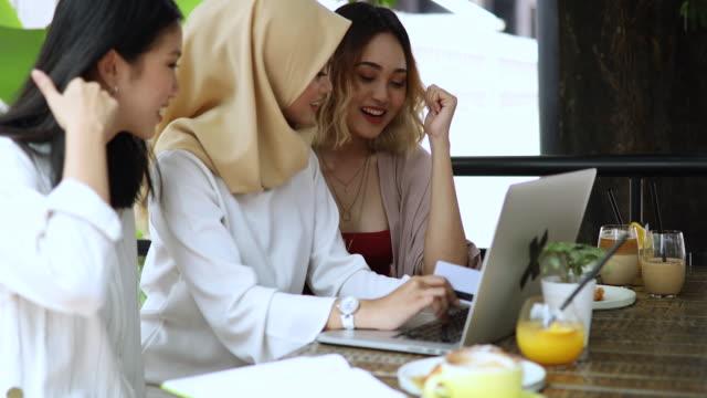 vidéos et rushes de femmes avec hijab et ses amies travaillant dans le café - vêtement religieux