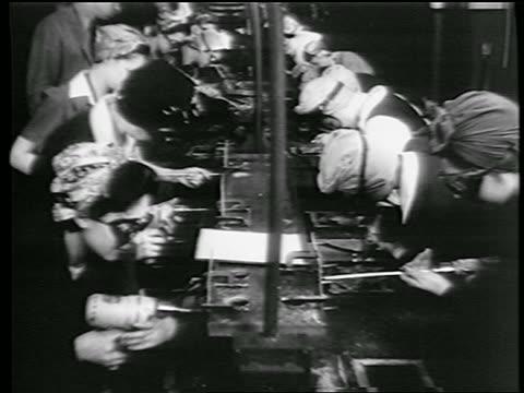 stockvideo's en b-roll-footage met b/w 1944 women with kerchiefs on heads riveting in defense plant / world war ii / industrial - first line of defense filmtitel