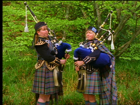 vídeos y material grabado en eventos de stock de 2 women with kilts playing bagpipes near forest / callander, scotland - escocia