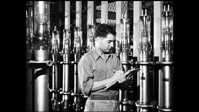 women with nail polish assembling light bulbs on the assembly line; man with clipboard checking on row of light bulbs mounted in glass tubes - 1940 1949 video stock e b–roll