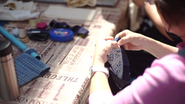 women with needle sewing patchwork in the workshop, handmade and handicraft concept. - embroidery stock videos & royalty-free footage
