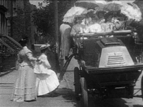 b/w 1905 women with parasols climbing into jitney / documentary - parasol stock videos & royalty-free footage
