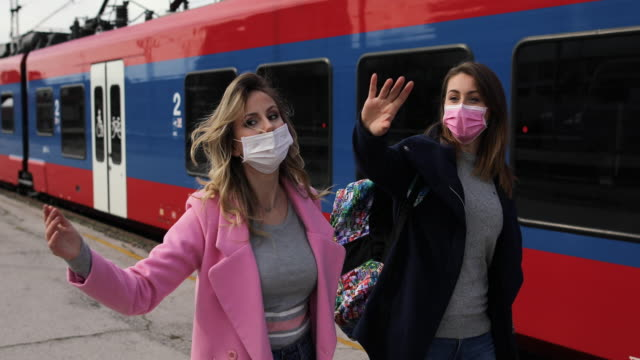 women with protective masks passing by the train at train station - station stock videos & royalty-free footage