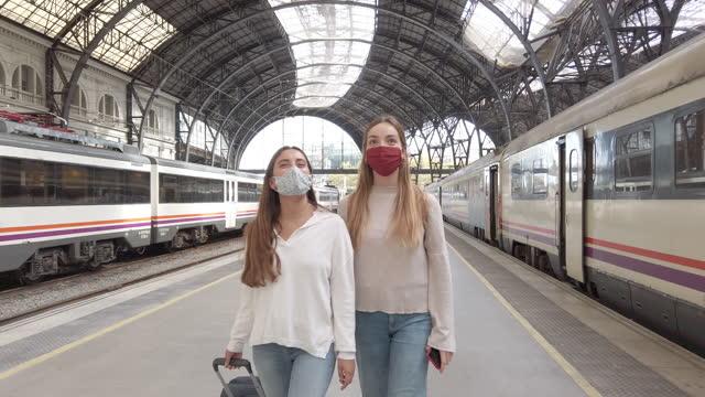 vídeos y material grabado en eventos de stock de mujeres con máscaras protectoras pasando por el tren en la estación de tren - estación entorno y ambiente