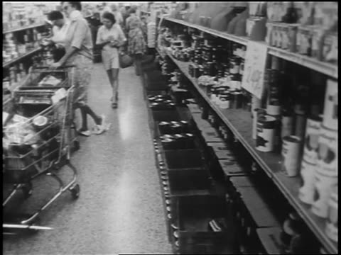 stockvideo's en b-roll-footage met b/w 1962 women with shopping carts in grocery store aisle during cuban missile crisis - koude oorlog