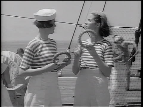 b/w 1934 2 women with striped shirts holding rings talking to each other on ship deck / ocean in background - 1934 stock-videos und b-roll-filmmaterial