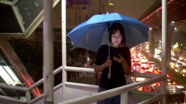 frauen mit schirm mit telefon im regen - sturm frau stock-videos und b-roll-filmmaterial