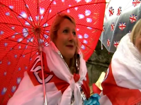 women with umbrellas and flags stand by the thames under the rain to see the river pageant in celebration of the queen elizabeth ii's diamond jubilee - bandiera inglese video stock e b–roll