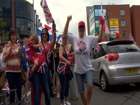 Women with Union Jack tshirts and flags dance during loyalist parade in Belfast September 2012