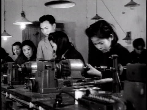 1944 women work in factory as supervisor watches / China