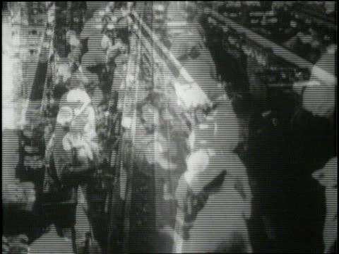 women work on an assembly line in a factory - 1900~1909年点の映像素材/bロール