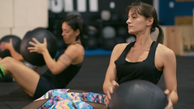 ms women work out with medicine balls in a gym / rio de janeiro, brazil - 床に座る点の映像素材/bロール