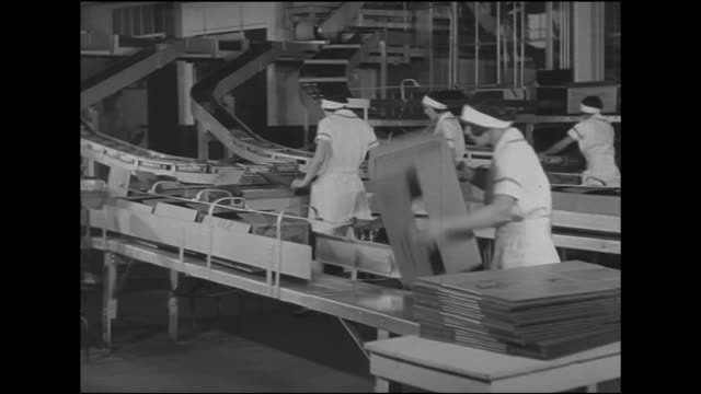 women workers assembling milky way boxes pushing into line on conveyor smaller boxes moving on higher curved conveyor being pulled by female hands... - pushing stock videos & royalty-free footage