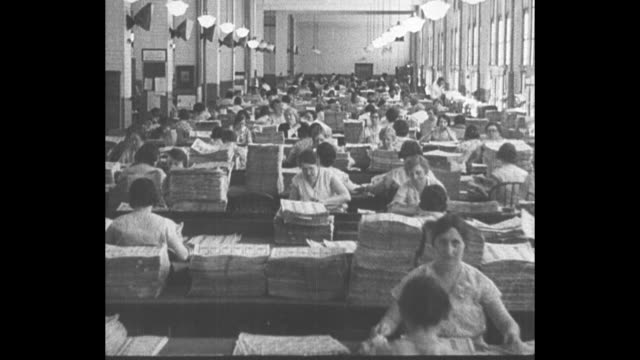 LS women workers at US Treasury Department in Washington DC sit at long tables work with stacks of uncut sheets of US currency / CU machine stamps...