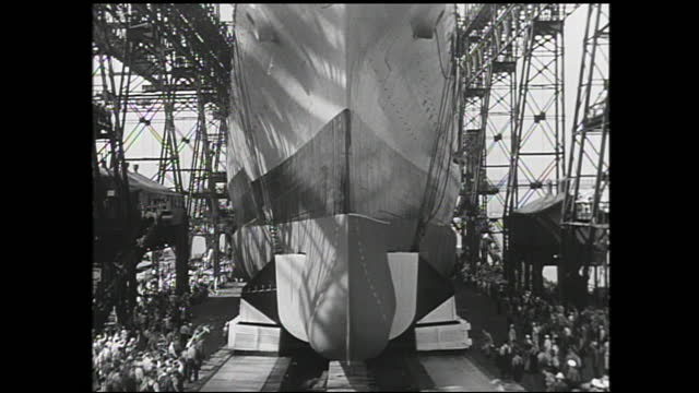 women workers working on the assembly line, assembled machine presented on table; tilt up view of large ship traveling on tracks surrounded by crowds... - 1940 1949 bildbanksvideor och videomaterial från bakom kulisserna